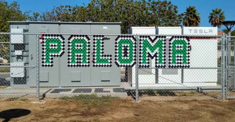 Picture of chain link fence with colored inserts spelling Paloma